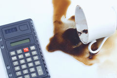 Coffee spill, coffee cup  and a calculator. Stock Photography