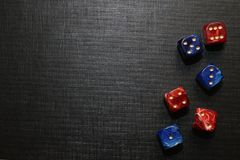 Coffee spilled on a black keyboard close-up. Multi-colored dice lying on a black textured surface Stock Image