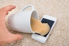 Coffee spilled on cellphone Stock Images
