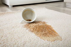 Coffee Spilling From Cup On Carpet. Close-up Of Coffee Spilling From Cup On Carpet Royalty Free Stock Photo