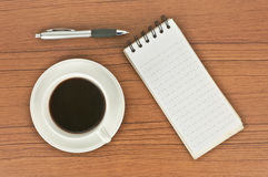 Coffee and spiral notebook. Top view of coffee cup, spiral notebook and pen on the wooden table Royalty Free Stock Photo