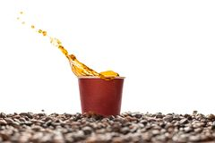Coffee splash in brown disposable paper cup with coffee beans isolated on white. Concept: coffee advertising stock photo