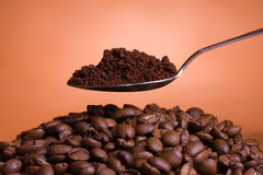 Coffee spoon. Spoon with ground coffee held over roasted coffee beans stock images