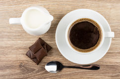 Coffee, spoon, pieces of chocolate and milk jug. On wooden table. Top view Stock Photos