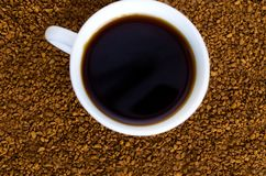 Coffee stands next to a white cup filled with hot coffee among scattered coffee beans, table, top view, horizontal stock photography