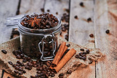 Coffee and star anise in jar. Coffee beans and star anise in jar with cinnamon on sackcloth on the wooden table Stock Photography