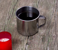 Coffee in a steel mug and the burning red candle Royalty Free Stock Photography