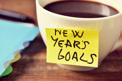 Coffee and a sticky note with the text new years goals Royalty Free Stock Photography