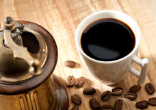 Coffee still-life. With cup and mill over wooden desk royalty free stock photography