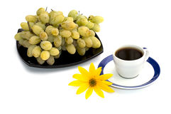 Coffee still life, black plate with grapes and a yellow flower Stock Photo