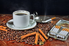 Coffee still life with a cigarette case and cigarettes. Still life with a cup of coffee, coffee grains, cinnamon and cigarettes Royalty Free Stock Photos