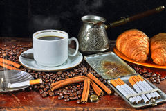 Coffee still life with a cigarette case and cigarettes. Still life with a cup of coffee, coffee grains, cinnamon, croissants and cigarettes Royalty Free Stock Photos