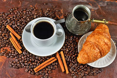 Coffee still life. Still life with a cup of coffee, coffee grains, cinnamon and croissants Royalty Free Stock Image