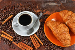 Coffee still life. Still life with a cup of coffee, coffee grains, cinnamon and croissants Stock Photo