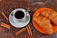 Coffee still life. Still life with a cup of coffee, coffee grains, cinnamon and croissants Stock Photography