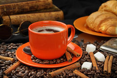 Coffee still life with an orange mug, croissants and books. Still life with coffee grains, sugar, cinnamon, antiquarian books and an orange cup of coffee Royalty Free Stock Image