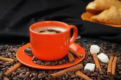 Coffee still life with an orange mug and croissants. Still life with coffee grains, sugar, cinnamon, croissants and an orange cup of coffee Stock Photo