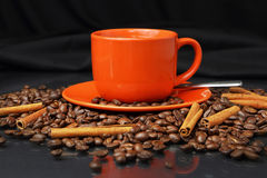 Coffee still life with an orange mug. Still life with coffee grains, cinnamon and an orange cup of coffee Royalty Free Stock Photo
