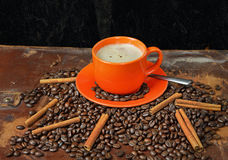 Coffee still life with an orange mug. Still life with coffee grains, cinnamon and an orange cup of coffee Royalty Free Stock Photography