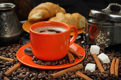 Coffee still life with an orange mug. Still life with coffee grains, sugar, cinnamon, croissants and an orange cup of coffee Royalty Free Stock Photos