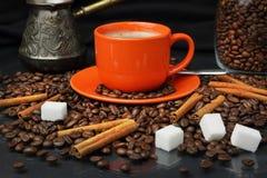Coffee still life with an orange mug. Still life with coffee grains, sugar, cinnamon and an orange cup of coffee Royalty Free Stock Image