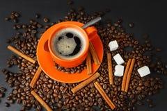 Coffee still life with an orange mug. Still life with coffee grains, sugar, cinnamon and an orange cup of coffee Stock Photography
