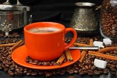 Coffee still life with an orange mug and a sugar bowl. Still life with coffee grains, sugar, cinnamon, sugar bowl and an orange cup of coffee Royalty Free Stock Photos