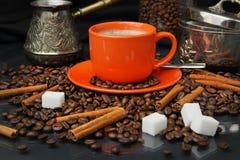 Coffee still life with an orange mug and a sugar bowl. Still life with coffee grains, sugar, cinnamon, sugar bowl and an orange cup of coffee Stock Photos
