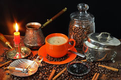 Coffee still life in a retro style. With an orange mug, grains coffee, jam and a candle Royalty Free Stock Photo