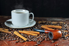 Coffee still life with a tube for smoking. Still life with a cup of coffee, coffee grains, cinnamon and a tube for smoking Stock Photos