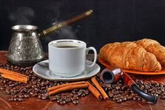 Coffee still life with a tube for smoking. Still life with a cup of coffee, coffee grains, cinnamon, croissants and a tube for smoking Stock Image