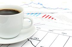 Coffee And Stock Chart. A tasty cup of coffee with the stock charts royalty free stock photo