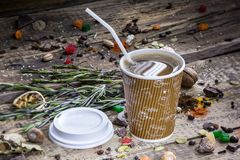 Coffee with a straw. A  brown and white striped mug of coffee with a straw and the lid lying on a bench beside it with odds and ends from a garden strewn about Royalty Free Stock Images