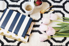 Coffee, strawberries, notebooks on Scandinavian rug. Pink Tulips and Gold Spoons. White black pattern and gold theme. Lifestyle co Royalty Free Stock Images