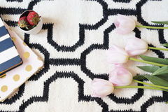 Coffee, strawberries, notebooks on Scandinavian rug. Pink Tulips and Gold Spoons. White black pattern and gold theme. Lifestyle co Stock Images