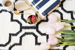 Coffee, strawberries, notebooks on Scandinavian rug. Pink Tulips and Gold Spoons. White black pattern and gold theme. Lifestyle co. Ncept. Copy Space Royalty Free Stock Photo