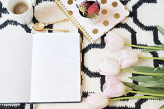 Coffee, strawberries, notebooks on Scandinavian rug. Pink Tulips and Gold Spoons. White black pattern and gold theme. Lifestyle co. Ncept. Copy Space Royalty Free Stock Photos