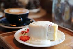 Coffee and strawberry cream cake on wooden tray