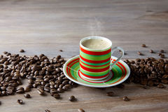 Coffee in striped cup with beans Royalty Free Stock Image
