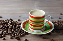 Coffee in striped cup with beans Stock Images