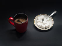 Coffee and sugar. A cup of coffee and sugar-cubes on a plate Stock Photos