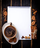 Coffee, sugar, cinnamon, cookies and open notebook Stock Photography