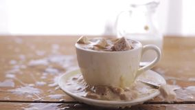 Coffee and sugar falling to cup on table. Unhealthy eating, diabetes, object and drinks concept - coffee and lump sugar falling to cup and splashing all over stock video