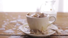 Coffee and sugar falling to cup on table. Unhealthy eating, diabetes, object and drinks concept - coffee and lump sugar falling to cup and splashing all over stock footage