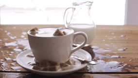 Coffee and sugar falling to cup on table. Unhealthy eating, diabetes, object and drinks concept - coffee and lump sugar falling to cup on wooden table stock video footage