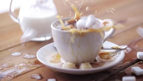 Coffee and sugar falling to cup on table. Unhealthy eating, diabetes, object and drinks concept - coffee and lump sugar falling to cup on wooden table stock video