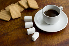Coffee, sugar lumps and cookies. On a wooden table Royalty Free Stock Photo