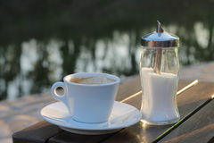 Coffee and sugar. Outside near the water Royalty Free Stock Photography