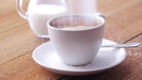 Coffee and sugar pouring to cup on table stock footage