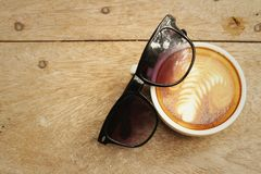 Coffee with sun glasses on background of wooden. Stock Images